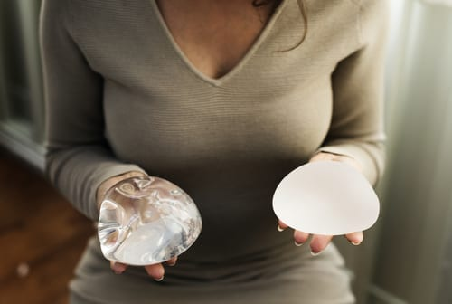 Woman Holding Saline and Silicone Breast Implants