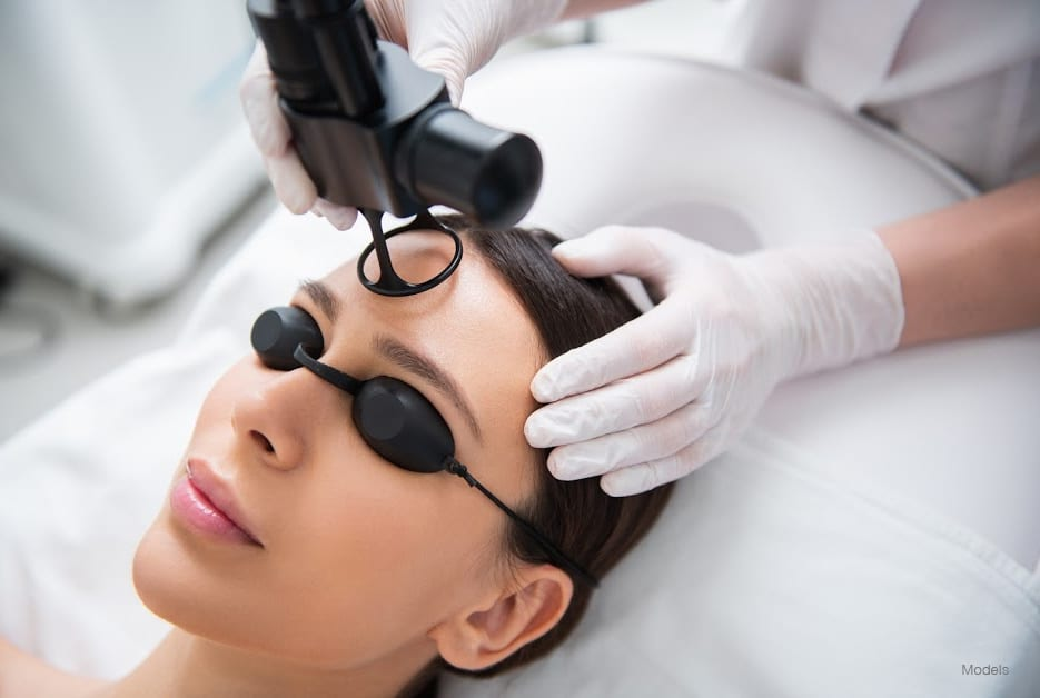 Anti-aging body treatment. Close up top angle portrait of pretty relaxed woman in eyeglasses having laser fractional rejuvenation of forehead