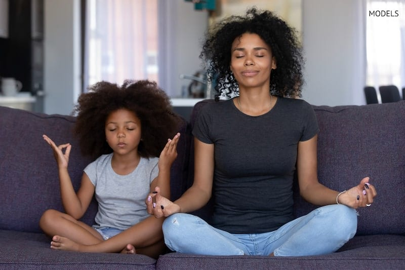 Young mother meditating with her daughter on the couch.